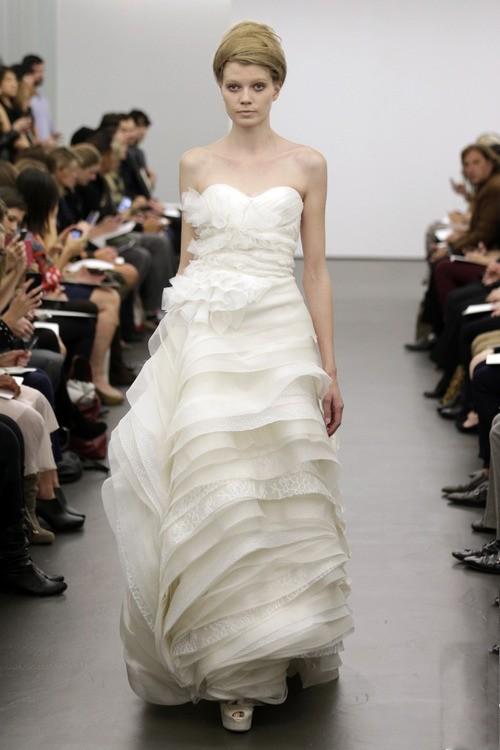 Robe de mariée bustier ivoire avec une jupe étagée fluide signée vera wang.