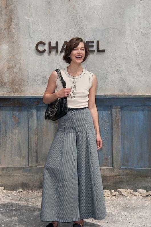 Milla Jovovich est vêtue d'une jupe longue à rayures au défilé Chanel haute couture au Grand Palais