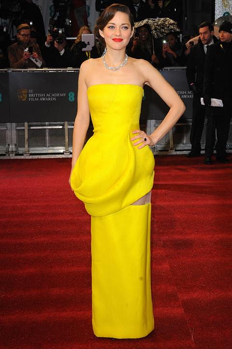 L'actrice française Marion Cotillard porte une robe de soirée bustier jaune de la maison Dior.