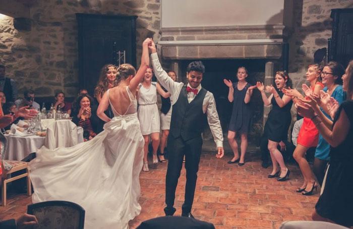 mariée en une robe de mariée fluide dos nu danse avec le marié