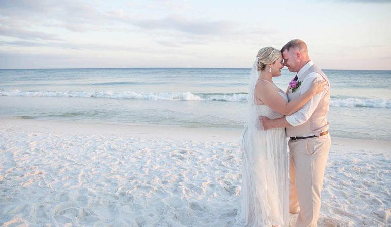 couple s'embrasse sur la plage portant des vêtements de mariage