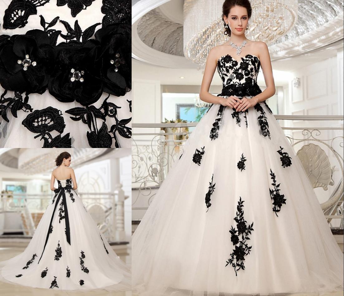 robe de mariée blanche princesse couvert en dentelle appliquée de fleurs noires et ceinturé de fleurs fait-main
